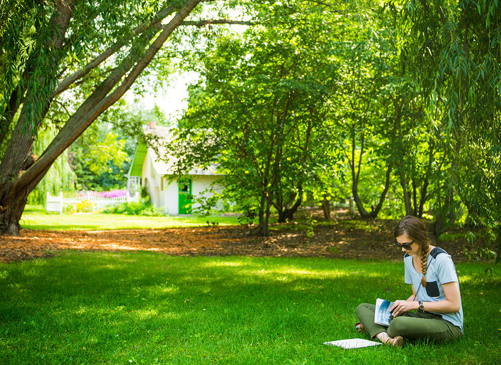 Woman sitting in grass reading a book